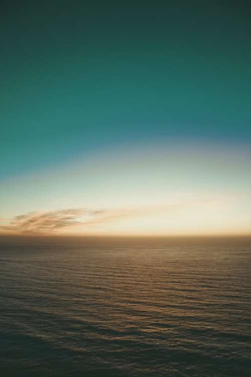 Teal Sky Over Calm Evening Waters Photo