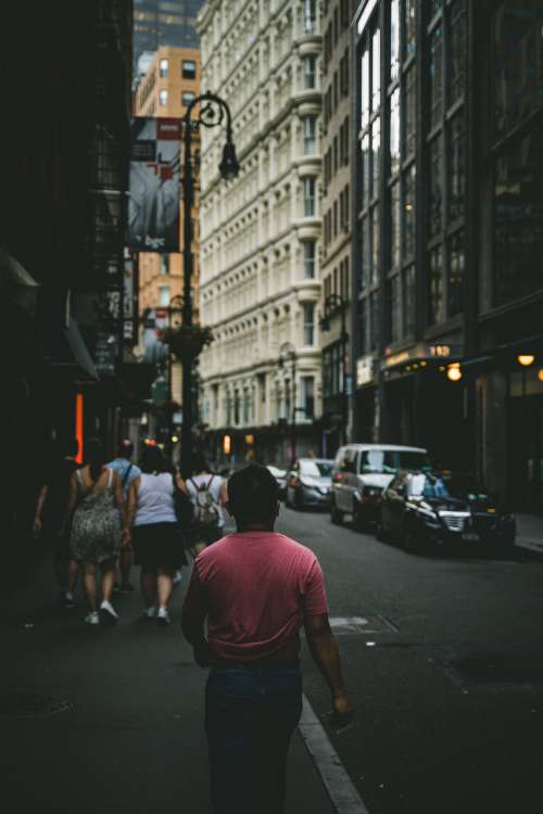 Man In Red T-Shirt Walks Through City Photo