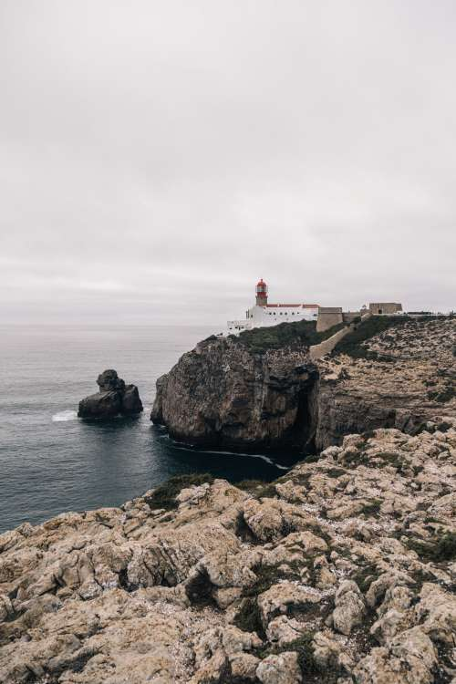 A Lighthouse Watches Over A Rocky Coastline Photo