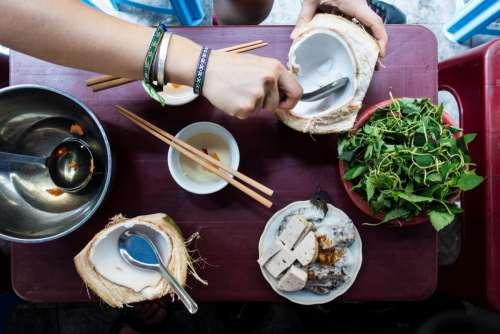 Eating coconut in a Vietnamese street food market