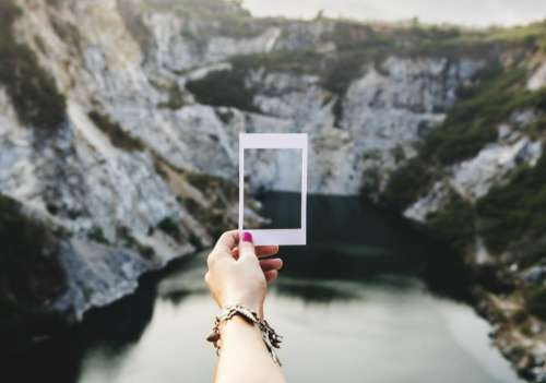 Female hand holding a photo frame shaped paper cut out template outdoors