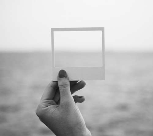 A hand holding a photo frame shaped paper cut out