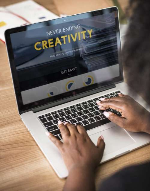 Close up of a woman typing Creativity on the laptop