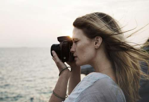 Side view of a young woman taking photograph at sunset
