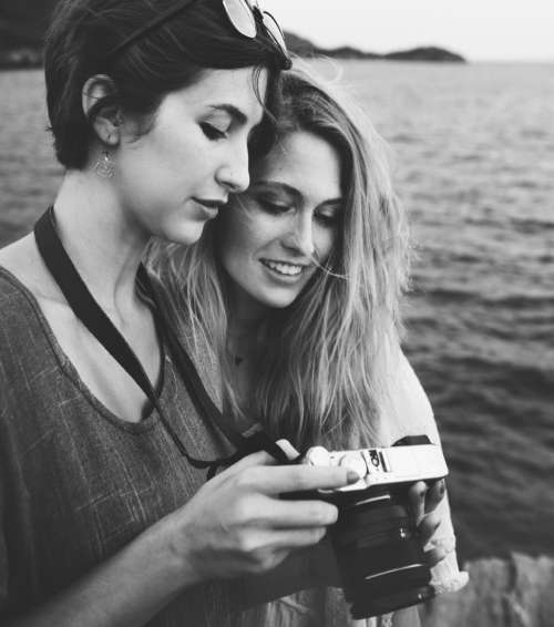 Two young caucasian women looking at their photograph on the camera display by the sea