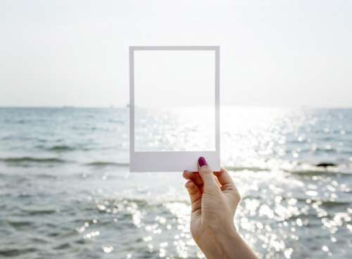 A female hand holding a photo frame shaped paper cut out template