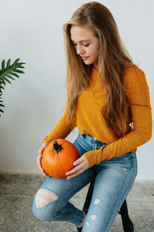 A young girl holds a pumpkin in her hand