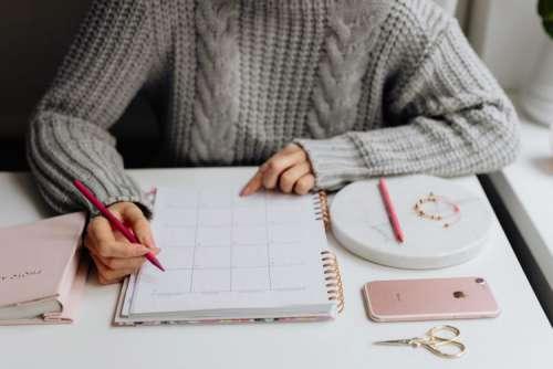 A woman writes in a calendar