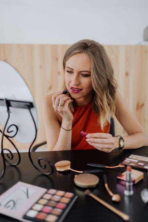 Young woman sitting and doing makeup in front of mirror