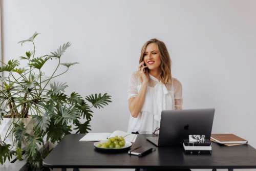 A businesswoman works at a desk with a laptop