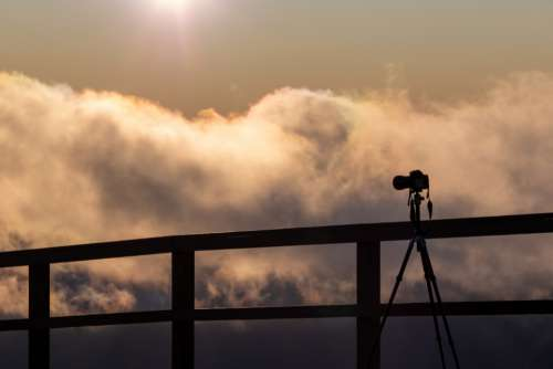 camera silhouette sky tripod clouds