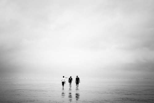 Three Men Walk Out Over A Low-Tide Beach Photo