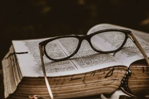 Black Spectacles Otop An Open Book Photo