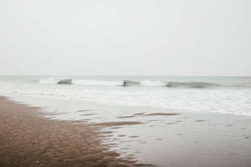 Waves Roll Up To The Sandy Beach On A Overcast Day Photo