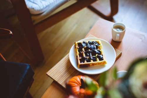 Homemade pumpkin waffle with dark chocolate topping and coffee