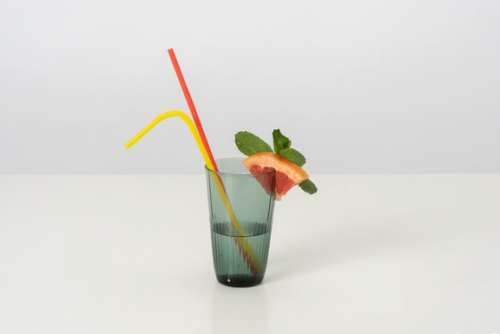 A Glass Of Cold Water With A Slice Of Grapefruit And Some Mint Leaves On It, With Two Colorful Plastic Straws Because Drinking From Both At The Same Time Is Double Fun