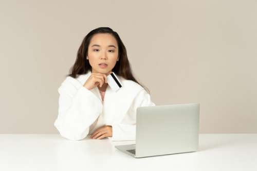 Young Asian Woman Looking Distracted While Doing Online Shopping