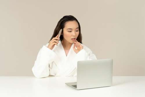 Young Asian Woman Talking On The Phone While Doing Online Shopping