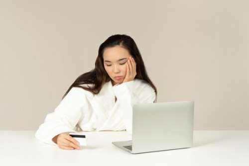 Bored Young Asian Woman Doing Online Shopping