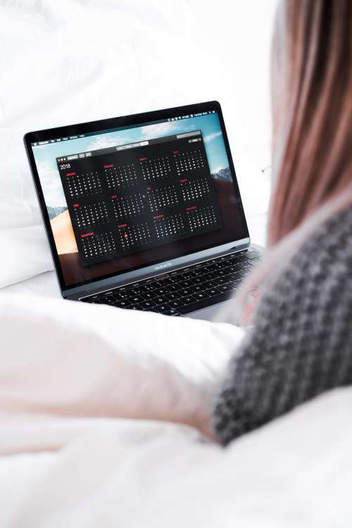 Woman Planning Her Calendar in Bed Free Photo