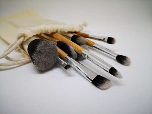A Group Of Paint Brushes Spill Out Of A Cream Linen Bag Photo