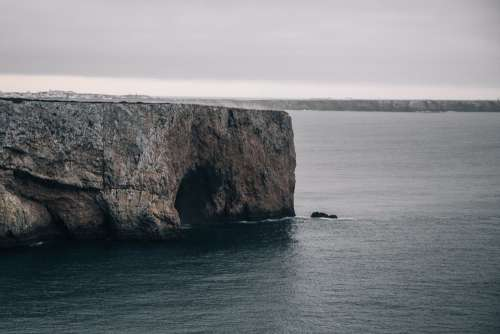 A Cave Gulps In Icy Water Out The Side Of A Cliff Photo