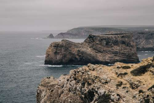 A Big Stone Outcrop Stands Apart From Cliffs In The Grey Sea Photo