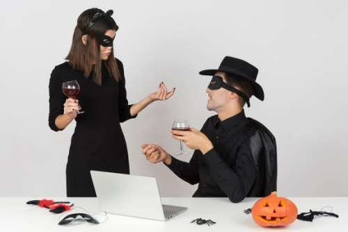 Woman In Cat Costume And Her Coworker In Zorro Costume Looking At Something At Notebook