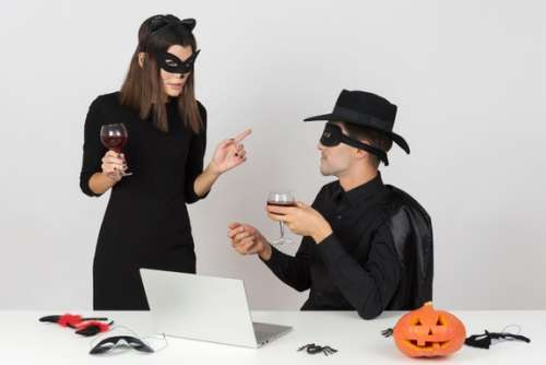 Female Worker In Cat Costume Talking To Male Colleague Dressed Like A Zorro