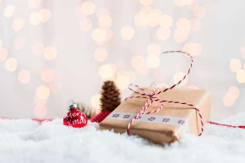 Christmas Present in Snow with Bokeh Background Free Photo