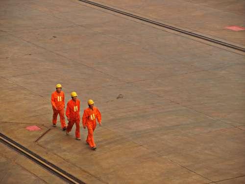 workers helmets outdoors industrial tarmac