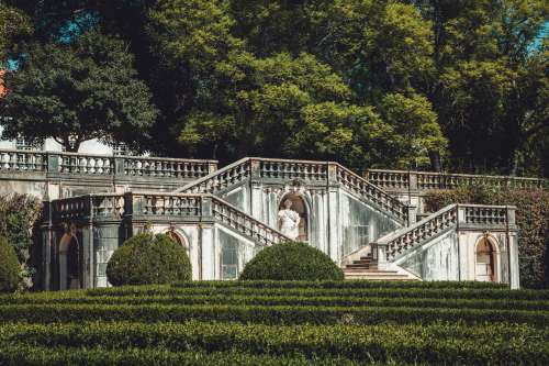Lush Green Hedges Surround Carved Marble Stairs And Statues Photo
