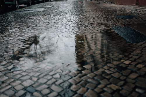 Puddle On A Cobble Street Photo