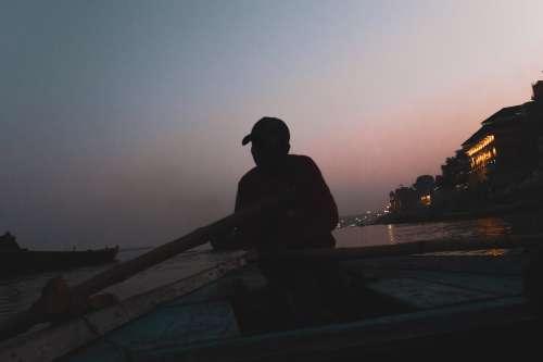 Man Rowing A Boat At Dusk Photo