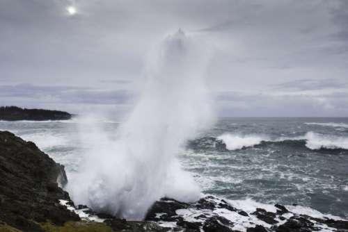 waves crashing rocks coast shore