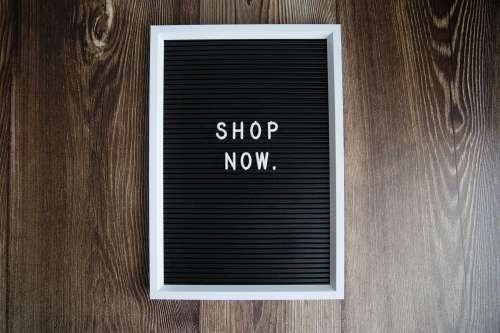 Shop Now Sign On Dark Wood Photo