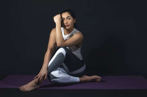 Woman Lens On Hand While Sitting On Yoga Mat Photo