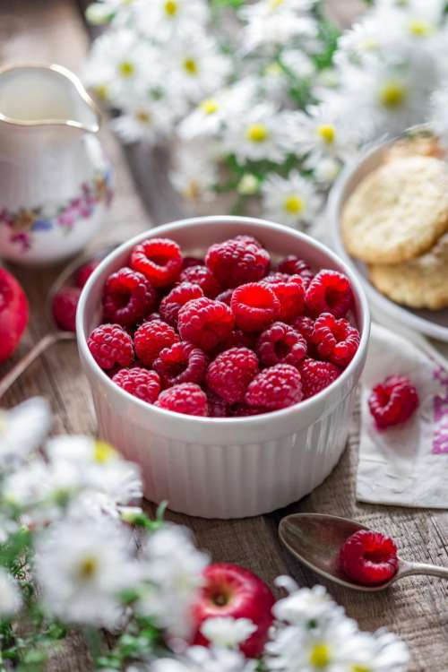 Close up of a bowl of raspberries on a spring themed table