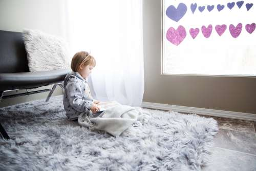 A Small Child Reads Near A Window Photo