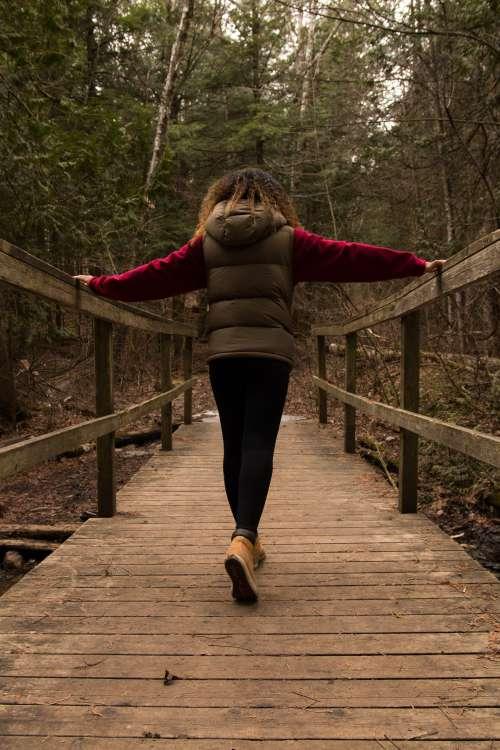 Woman Walks Across Bridge In Forest Photo