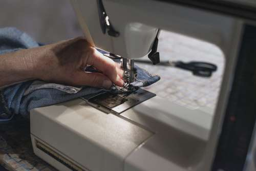 Hand Uses Sewing Machine On Denim Photo