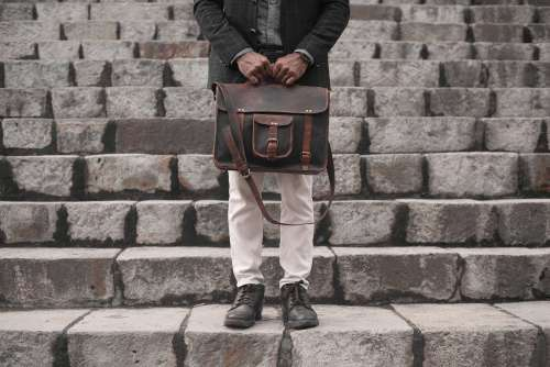 Man Holding A Leather Bag On A Set Of Stairs Photo