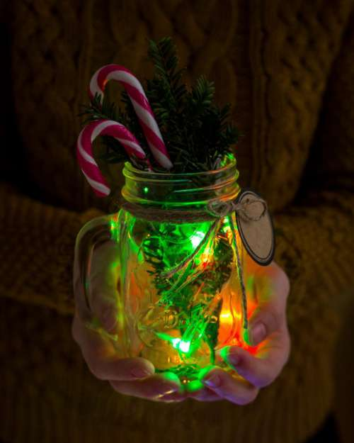 Close up of hands holding a mason jar with Christmas decorations