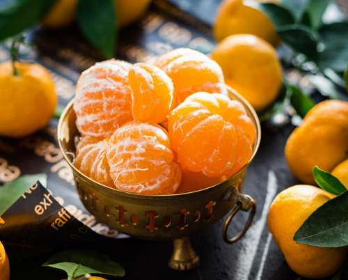 Close up of peeled mandarins in a brass fruit bowl