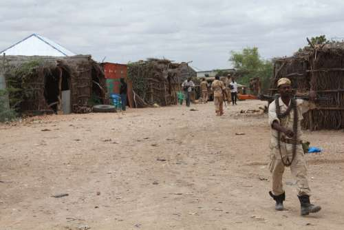 people, home, man, war crisis, hut, military, weapon, rifle, uniform, belt of bullets, walk, patrol, rural place