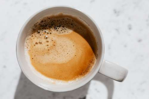 A cup of coffee on white marble