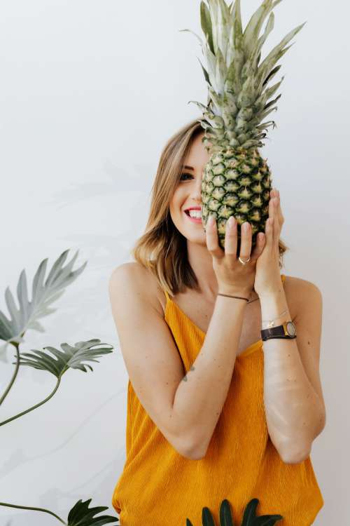 A beautiful smiling young woman is holding a pineapple