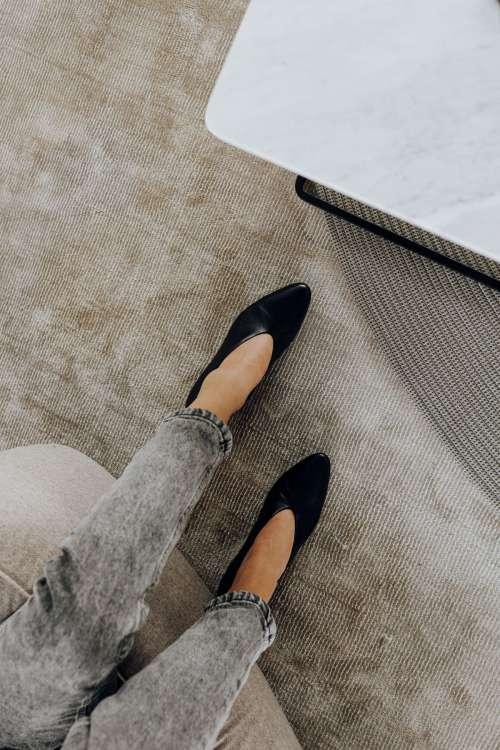 Woman wearing grey jeans & black leather high heels