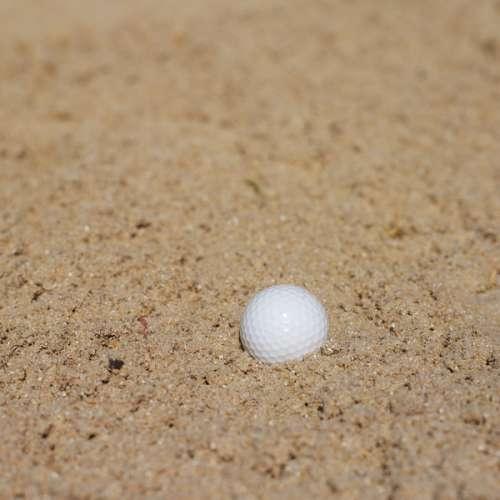 Golf ball lying in a sand bunker