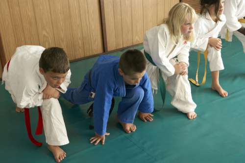 five martial arts students stretching